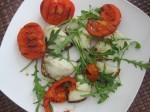 light snack: roasted sunflower bread with melted cheese, fresh rucola and grilled tomatoes